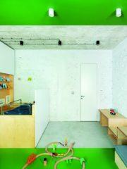 Авторите на проекта интегрират всички инсталации в корпусната мебел - така е и в детската стая, където климатизацията и проекторът са напълно невидими. Тук са използвани любимите цветове на детето и игрови детайли, като в същото време е продължена естетиката от интериора. Тухлите са олекотени и успокоени, боядисани в бяло. Дори в рамките на сравнително малката стая има зониране, постигнато с мебелите и настилките. Корпусната мебел се превръща в шкаф, пейка, бюро, без да накъсва пространството.