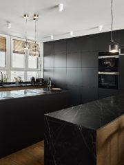Кухнята е с остров с котлони и вграден аспиратор. Плотовете са от 10 мм технически камък с декор черен мрамор (Стоун център). Плътната тъмна редица шкафове е балансирана от светлата, изцяло остъклената стена над мивката.