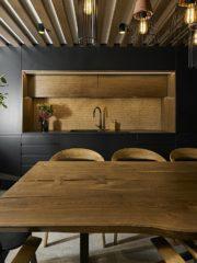 Винарната на приземния етаж е с подчертано по-тъмна тоналност. Столовете и масата са с красива извивка и не са с традиционно по-грубия силует на мебелите за механа. Любопитно е, че гърбът на кухненската мебел е от корк. Интересна е комбинацията на модерните черни обеми и провансалските греди на тавана. Осветлението е с главна роля за настроението.