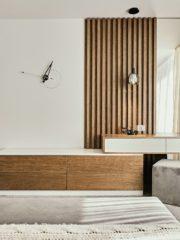 Родителската спалня е обзаведена минималистично в бяло и дърво.