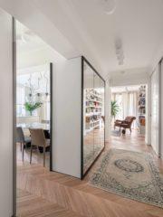 Апартаментът е с много прозорци и след като обединихме старите помещения, навсякъде прониква зеленина и светлина. Един от акцентите в проекта е двустранното огледало към антрето и трапезарията, което прикрива съществуваща колона и изпълнява функцията на шкаф за обувки от страната на антрето. Диван на Tommy M (Sklada), фотьойли Eiccholtz (Sklada) и Eames Plastic Armchair (Vitra). Основното осветление е от Artemide и Dekko.