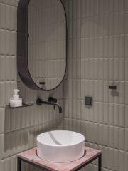 Матовите, релефни, пастелно зелени плочки в банята са съчетани с черни смесители и аксесоари.