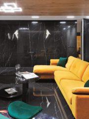 High-end комбинацията от камък, месинг и дърво, черно, бяло и златисто сдържано внушава класа. Щедрите меки обеми на софата, креслото, трапезарните столове балансират атмосферата с чувственост и интимност.