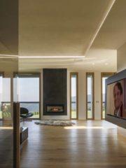 """Въпреки големия си размер, дневната внушава чувство за уют благодарение на използваните материали и доброто разположение на мебелите спрямо всички основни акценти на пространството. Във фокуса на дневната са висяща камина и декоративна интериорна стена с телевизор 85"""", а за фон служат големи френски прозорци, през които се разкрива впечатляваща гледка към езерото Панчарево и Лозен планина. Голямо внимание при проектирането е отделено на осветлението. То e в пълна хармония с избрания подход в дизайна на къщата. Използвана е разнообразна система точкови осветителни тела и линеарно осветление, вградени в таваните и стените, която намира приложение и в другите пространства на сградата"""