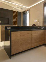Кухнята е организирана около два основни елемента – голям Г- образен кухненски плот и вградена кухненска мебел по дължината на една от стените. Г-образният плот завършва с барплот в средата на помещението, като седящите на него могат да наблюдават цялото пространство. На този плот с поглед към трапезарията е разположена мивката, а печката е наблизо – точно пред прозореца, през който се вижда цялата зона около басейна. За целта е избрана специална кухненска печка с вграден абсорбатор, с което се освобождава погледът навън. Кухнята е отделена от трапезарията чрез стъклена врата и плътна стена, на която централно за кухнята е разположен телевизор.