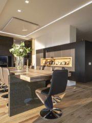 Просторната трапезария с маса за 12 човека действа като обединяващ елемент между кухнята и дневната и в същото време е обособена като самостоятелен кът. Централно срещу масата е разположен телевизор, удобен за гледане от всички места.