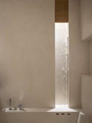 Ефектен дизайн на банята е постигнат чрез комбинация от микроцимент и дърво.