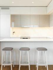Кухнята в бяло отразява светлината, създава усещане за чистота и съвършенство, изчистените обеми следват общия тон на интериора.