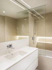 Баните са проектирани да бъдат прости и изчистени с ослепително бели плотове и безшевни мивки Corian.