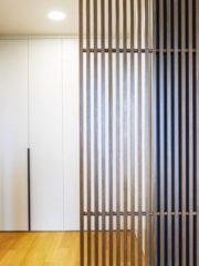 Гардеробното в основната спалня е отделено с ефирни дървени плъзгащи се решетки, пропускащи естествена светлина вътре. Играта с повтарящи се дървени елементи продължава в стената срещу леглото.