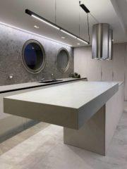 """Независимо от многото метаморфози на кухнята като материали, структурата й остава винаги една и съща. Подчертаната категорична надлъжна линия се запазва, а """"летящият"""" остров е центърът, около който се организира всичко. Шкафовете са изпълнени с плоскости, имитиращи бетон. С подобни панели са облицовани и двете къси стени в помещението. Кръглите прозорци и цилиндричните аспиратори са акцента в градацията на аскетичните материали – бетон, камък, метал, детайли в черно. Така след разработване на много варианти, след трудни решения и забавени доставки в пандемията, кухнята е центърът на този дом. За сина, веган и йога, това е място от особена важност."""