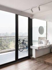 """В спалнята на бащата особено внимание е обърнато на банята. Тя, както и дрешникът, се приобщава към стаята, само душът и тоалетната остават в интимна ниша. Хладната комбинация от дискретни материали е """"стоплена"""" от настилката – за тази стая е избрано дърво. Гледката доминира над останалите детайли в пространството. Елементите в банята – мивката и батериите, внесени от италианската фабрика GESSI, мраморният плот, мраморната глава в душа придават рафинираност на помещението."""