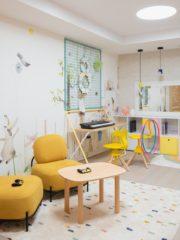 """Детският кът за игра предлага възможност за различни активности – стена за катерене, караоке и play station зони, музикално пространство, детска библиотека и широко бюро за рисуване. Игрив тапет внася настроение, а цветовете са меки, с акцентен жълт тон. Предвидени са вградени шкафове за съхранение на играчките, които се сливат прекрасно със зоната на катерене и оформят меки """"убежища""""."""